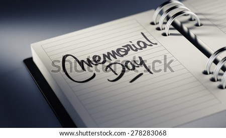 Closeup of a personal agenda setting an important date representing a time schedule. The words Memorial Day written on a white notebook to remind you an important appointment.
