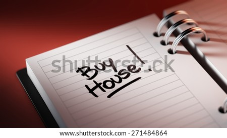 Closeup of a personal agenda setting an important date representing a time schedule. The words Buy House written on a white notebook to remind you an important appointment.