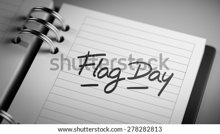Closeup of a personal agenda setting an important date representing a time schedule. The words Flag Day written on a white notebook to remind you an important appointment.