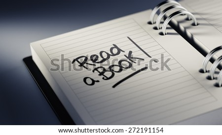 Closeup of a personal agenda setting an important date representing a time schedule. The words Read a book written on a white notebook to remind you an important appointment. - stock photo