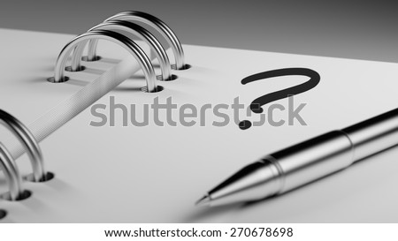 Closeup of a personal agenda setting an important date writing with pen. Question Mark written on a white notebook to remind you an important appointment.