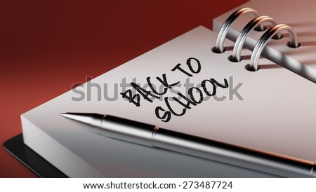 Closeup of a personal agenda setting an important date writing with pen. The words Back to school written on a white notebook to remind you an important appointment.