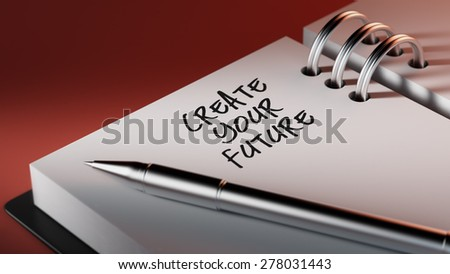 Closeup of a personal agenda setting an important date writing with pen. The words Create your future written on a white notebook to remind you an important appointment.