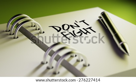 Closeup of a personal agenda setting an important date writing with pen. The words Don't Fight written on a white notebook to remind you an important appointment. - stock photo