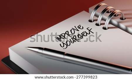Closeup of a personal agenda setting an important date writing with pen. The words Improve yourself written on a white notebook to remind you an important appointment.