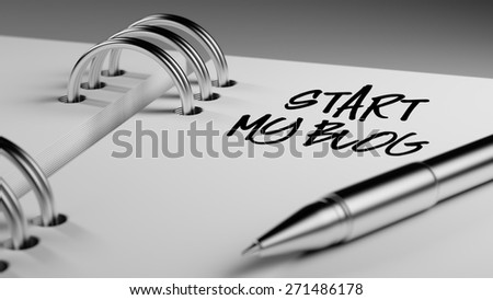Closeup of a personal agenda setting an important date writing with pen. The words Start my Blog written on a white notebook to remind you an important appointment. - stock photo