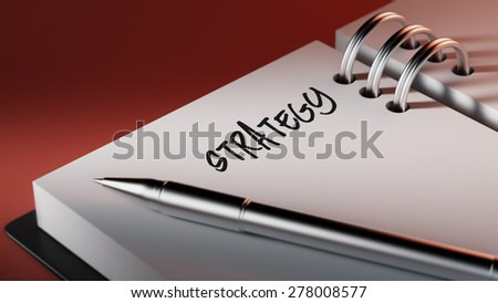 Closeup of a personal agenda setting an important date writing with pen. The words Strategy written on a white notebook to remind you an important appointment.