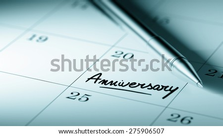 Closeup of a personal agenda setting an important date written with pen. The words Anniversary written on a white notebook to remind you an important appointment.