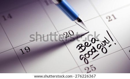 Closeup of a personal agenda setting an important date written with pen. The words Be a good girl written on a white notebook to remind you an important appointment.