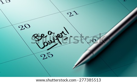 Closeup of a personal agenda setting an important date written with pen. The words Be a Lawyer written on a white notebook to remind you an important appointment.