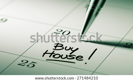 Closeup of a personal agenda setting an important date written with pen. The words Buy House written on a white notebook to remind you an important appointment.