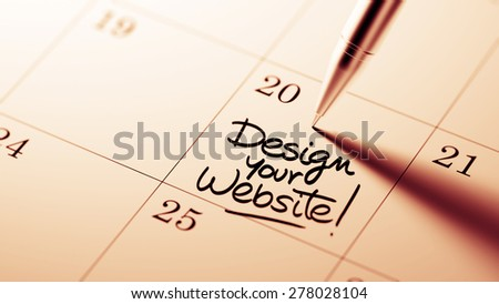 Closeup of a personal agenda setting an important date written with pen. The words Design your website written on a white notebook to remind you an important appointment.