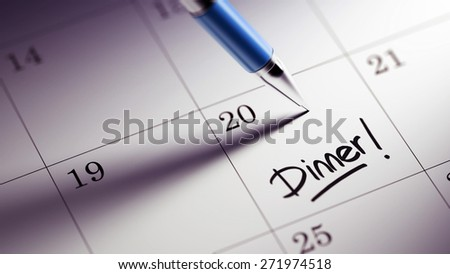 Closeup of a personal agenda setting an important date written with pen. The words Dinner written on a white notebook to remind you an important appointment.