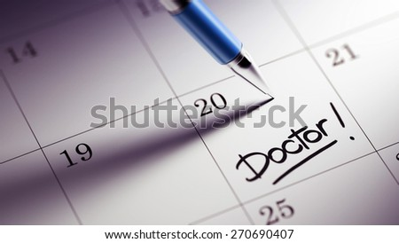 Closeup of a personal agenda setting an important date written with pen. The words Doctor written on a white notebook to remind you an important appointment.