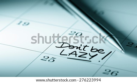 Closeup of a personal agenda setting an important date written with pen. The words Don't be Lazy written on a white notebook to remind you an important appointment.