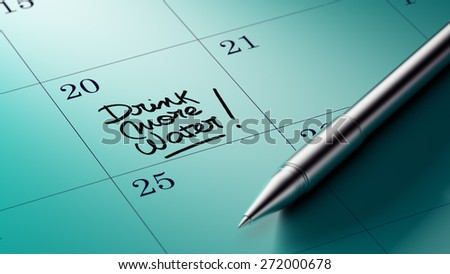 Closeup of a personal agenda setting an important date written with pen. The words Drink more water written on a white notebook to remind you an important appointment. - stock photo