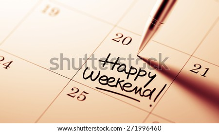 Closeup of a personal agenda setting an important date written with pen. The words Happy Weekend written on a white notebook to remind you an important appointment.