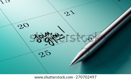 Closeup of a personal agenda setting an important date written with pen. The words Join GYM written on a white notebook to remind you an important appointment.