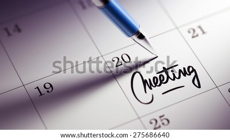 Closeup of a personal agenda setting an important date written with pen. The words Meeting written on a white notebook to remind you an important appointment.