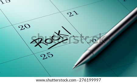 Closeup of a personal agenda setting an important date written with pen. The words Rock written on a white notebook to remind you an important appointment.
