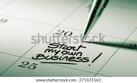 Closeup of a personal agenda setting an important date written with pen. The words Start my own Business written on a white notebook to remind you an important appointment.