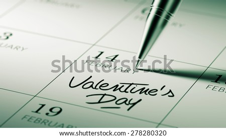 Closeup of a personal agenda setting an important date written with pen. The words Valentine's Day written on a white notebook to remind you an important appointment.
