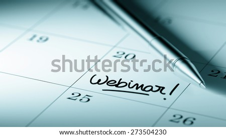 Closeup of a personal agenda setting an important date written with pen. The words Webinar written on a white notebook to remind you an important appointment.