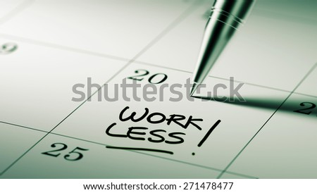Closeup of a personal agenda setting an important date written with pen. The words Work Less written on a white notebook to remind you an important appointment.