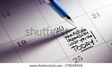 Closeup of a personal agenda setting an important date written with pen. The words Your future depends on what you do today written on a white notebook to remind you an appointment. - stock photo
