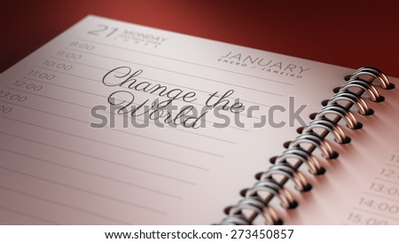 Closeup of a personal calendar setting an important date representing a time schedule. The words Change the world written on a white notebook to remind you an important appointment.