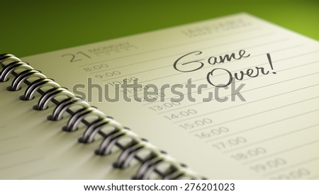 Closeup of a personal calendar setting an important date representing a time schedule. The words Game over written on a white notebook to remind you an important appointment.