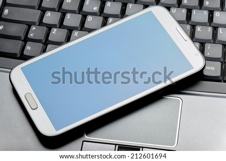 Closeup of a phablet on a laptop as concept of portable technology - stock photo