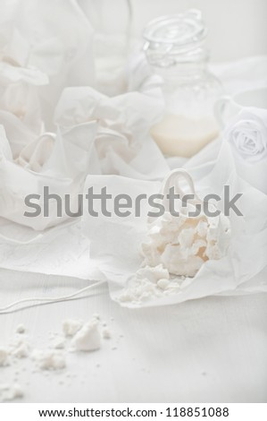 Closeup of a piece of broken meringue and the bottles with milk. Created with high key technique. - stock photo