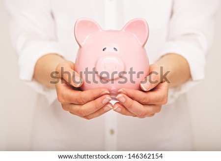 Closeup of a piggy bank in the hands of a woman