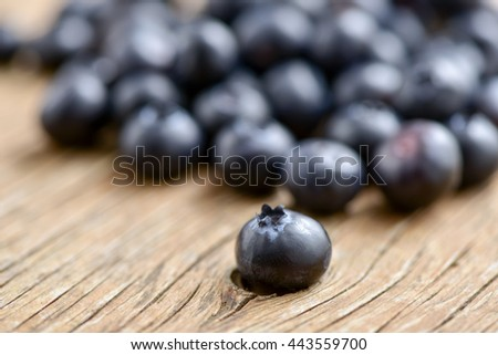 closeup of a pile of appetizing ripe blueberries on a rustic wooden table - stock photo