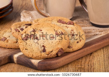 Closeup of a pile of chocolate chip cookies on a wooden board