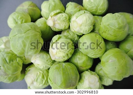 Closeup of a pile of fresh green Brussels sprouts on the black background. Healthy/clean eating concept; organic/unprocessed food; paleo diet. - stock photo
