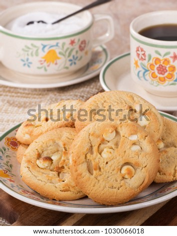 Closeup of a pile of macadamia nut cookies on a plate with coffee cup and sugar bowl in background