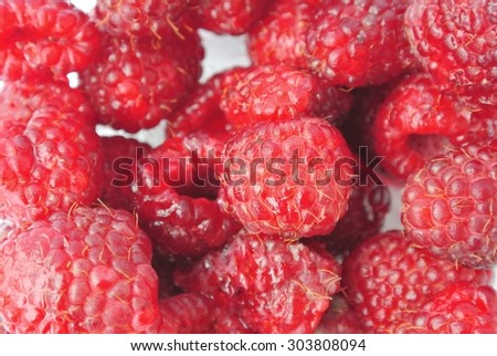 Closeup of a pile of ripe red juicy raspberries on white background. Concept of organic food; fresh, natural, healthy, unprocessed fruit: clean eating; paleo diet. - stock photo
