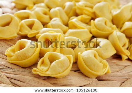 closeup of a pile of uncooked tortellini - stock photo