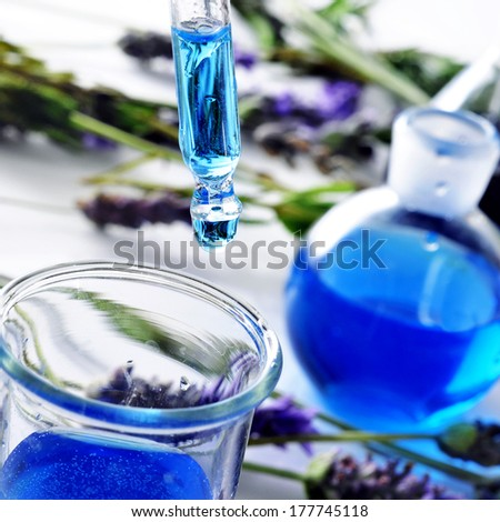 closeup of a pipette and a flask with flower essence and a pile of lavender flowers in the background - stock photo