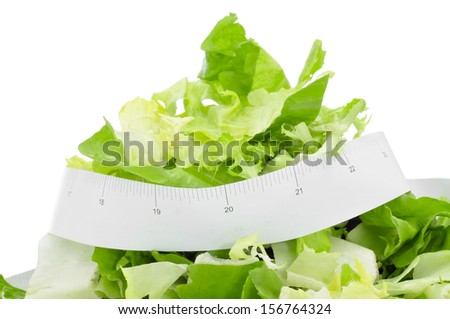 closeup of a plate with a green salad and a measuring tape, symbolizing the dieting concept or to stay fit