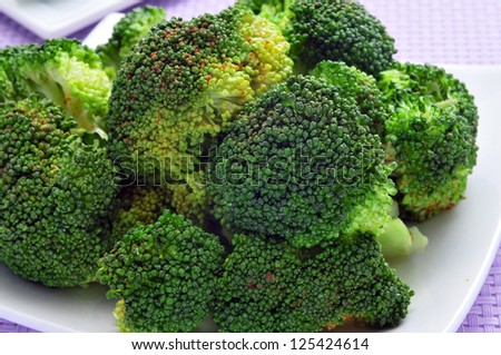closeup of a plate with cooked broccoli on a purple tablecloth - stock photo