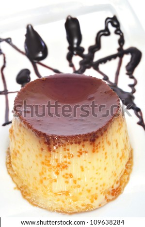 closeup of a plate with creme caramel ornamented with syrup - stock photo