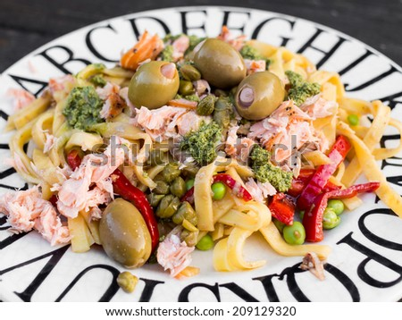 Closeup of a plate with pasta salad with salmon, olives and - stock photo