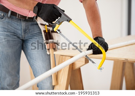 Closeup of a plumber using a hacksaw to cut down some pipes