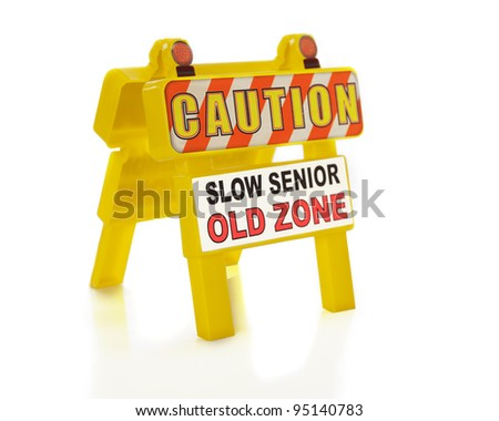 "Closeup of a portable road/sidewalk sign saying, ""Caution.  Slow Senior.  Old Zone.""  Shallow depth of field with focus on front words.  On a white background."