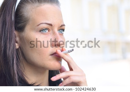 closeup of a pretty woman smoking at the street