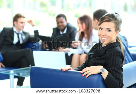 Closeup of a pretty young businesswoman smiling in a meeting with her colleagues in background - stock photo