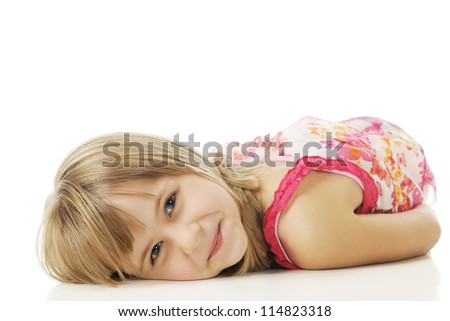 Closeup of a pretty young elementary girl happily resting on her belly.  On a white background. - stock photo